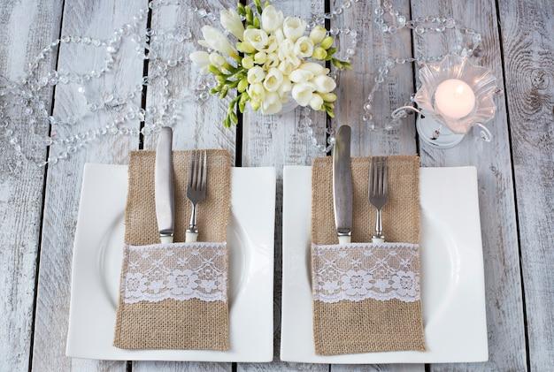 Em uma mesa de madeira branca, duas placas, velas, garfos e facas, flores em um vaso - um fundo festivo (aniversário, casamento, 8 de março, jantar romântico)