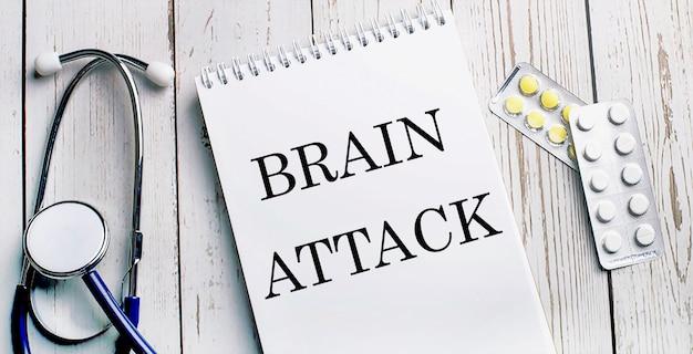 Em uma mesa de madeira clara, encontra-se um estetoscópio, pílulas e um caderno com a inscrição brain attack