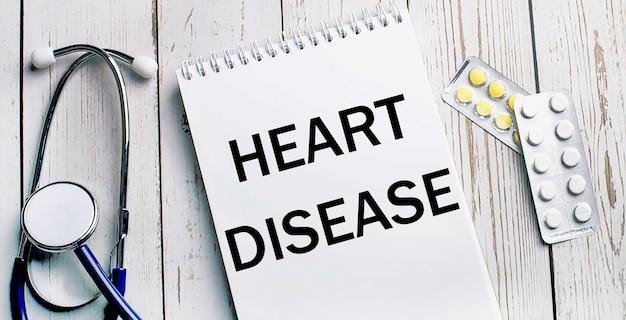 Em uma mesa de madeira clara, encontra-se um estetoscópio, pílulas e um caderno com a inscrição doença cardíaca