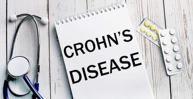Em uma mesa de madeira clara, encontra-se um estetoscópio, pílulas e um caderno com a inscrição doença de crohn