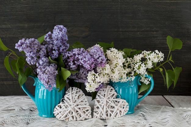 Em uma mesa de madeira, duas xícaras azuis com um buquê de lilás e dois corações de vime branco