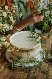 Em uma mesa de madeira é um bolo decorado com flores de camomila