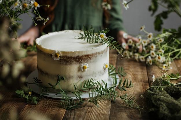 Em uma mesa de madeira é um bolo decorado com flores