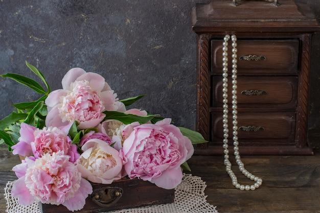 Em uma mesa de madeira em uma caixa decorativa peônias e uma caixa velha com pérolas de pérolas