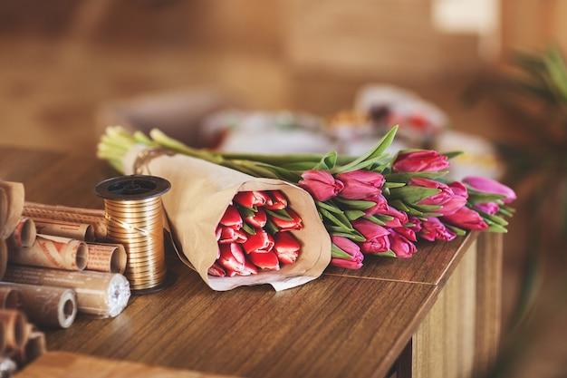 Em uma mesa de madeira encontra papel ofício fita de embrulho e tulipas cor de rosa. vista lateral