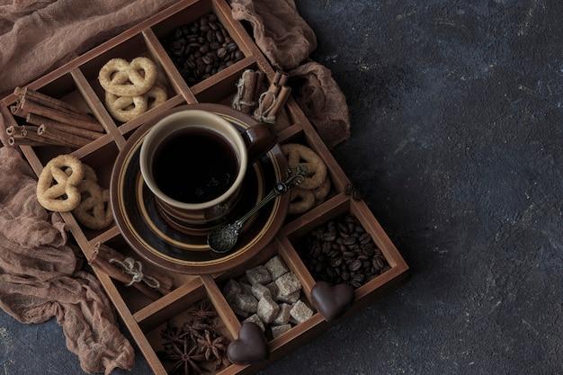 Em uma mesa de madeira escura, uma xícara de café, chocolate e pretzels em uma caixa