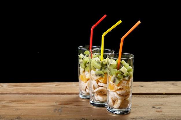 Em uma mesa de madeira estão três copos de frutas para um coquetel de frutas