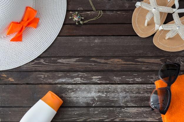 Em uma mesa de madeira flip-flops, óculos de sol, toalha, chapéu, protetor solar