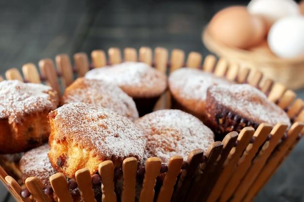 Em uma mesa de madeira, há cupcakes em uma cesta de pão de madeira