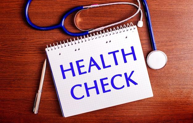 Em uma mesa de madeira, há uma caneta, um estetoscópio e um caderno com a etiqueta verificação de saúde. conceito médico