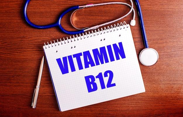 Em uma mesa de madeira, há uma caneta, um estetoscópio e um caderno com o rótulo vitamina b12
