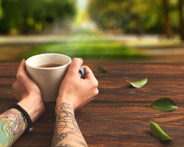 Em uma mesa de madeira marrom, uma xícara de chá verde em mãos femininas