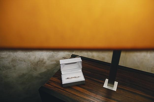 Em uma mesa de madeira perto de um candeeiro de mesa há uma caixa branca com anéis de casamento