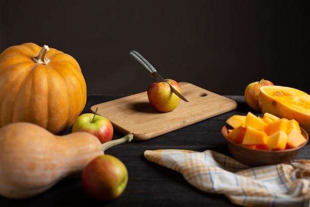 Em uma mesa de madeira preta, encontram-se abóboras de vários tamanhos e formas, maçãs maduras, um pano de prato e uma tigela de abóbora cortada.