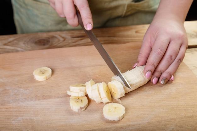 Em uma mesa de madeira sobre uma tábua de corte, uma mulher faz em pedaços uma faca de banana.