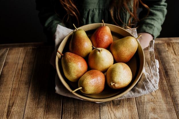 Em uma mesa de madeira um prato com nova colheita de peras
