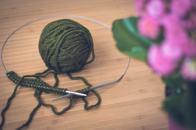 Em uma mesa de madeira uma bola verde de lã, raios de metal e uma flor rosa em uma panela