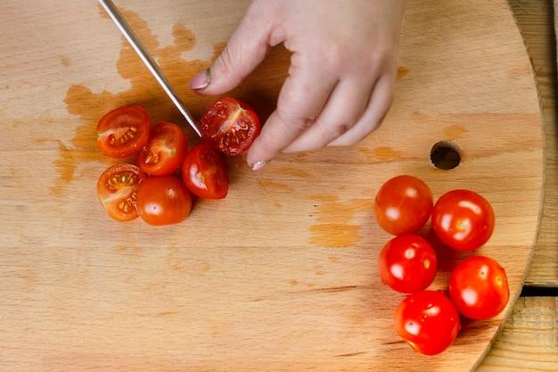 Em uma mesa de madeira, uma mulher corta tomates cereja para uma salada de legumes com uma faca.