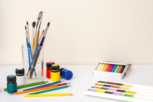 Em uma mesa de trabalho branca com material de desenho e escovas