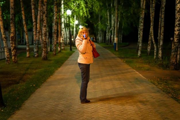 Em uma noite escura parque no caminho é uma mulher, ela está com medo, luzes da rua brilham, está escuro ao redor