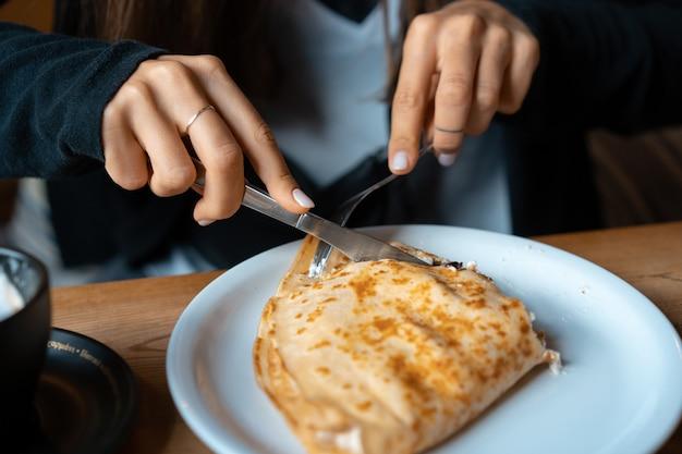 Em uma panqueca de prato com requeijão e cerejas.