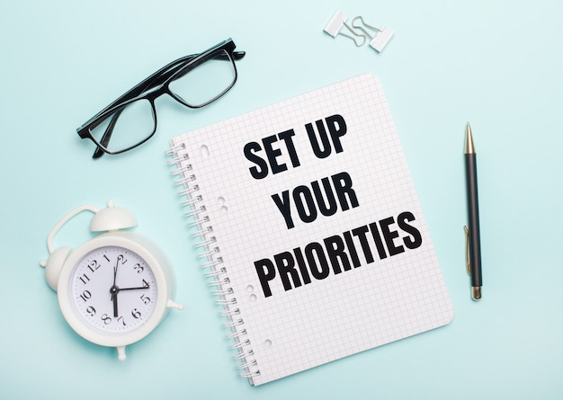 Em uma parede azul clara estão óculos pretos e uma caneta, um despertador branco, clipes de papel brancos e um caderno com as palavras configurar suas prioridades. conceito de negócios