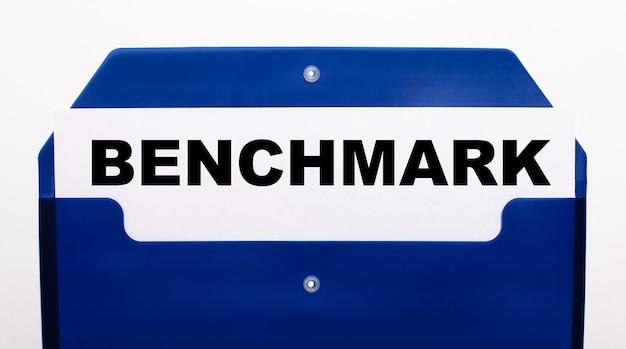 Em uma parede branca, uma pasta azul para papéis. na pasta, há uma folha de papel com as palavras benchmark.