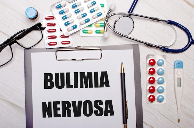 Em uma parede de madeira clara há papel com a inscrição bulimia nervosa, um estetoscópio, pílulas coloridas, óculos e uma caneta. conceito médico