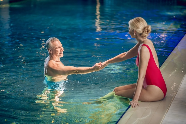 Em uma piscina. mulher loira bonita em um maiô vermelho passando um tempo na piscina com o esposo