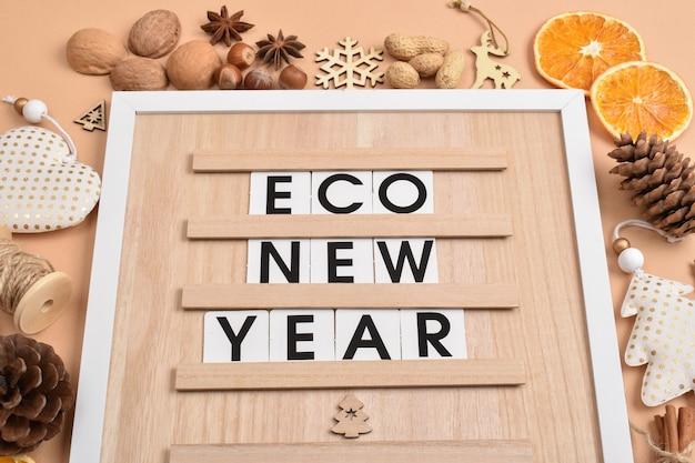Em uma placa de madeira, há uma inscrição econew year decorações naturais para o ano novo e o natal