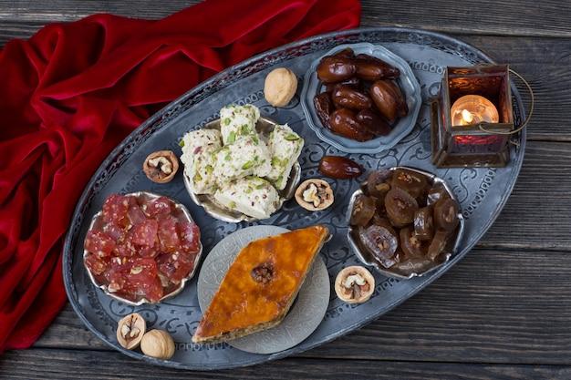 Em uma placa de prata datas, nozes, halva, delícia turca, baklava e uma lanterna