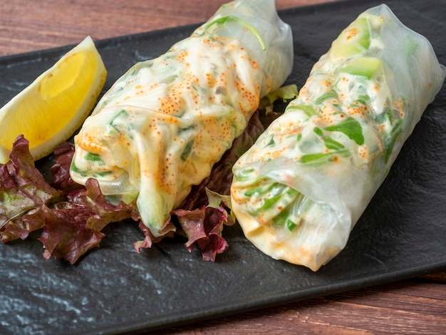 Em uma placa preta texturizada estão enrolados rolinhos primavera. um delicioso prato de dieta. cozinha asiática, close up