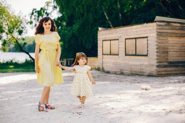 Em uma praia ensolarada com areia amarela, a mãe anda em um vestido amarelo e sua linda garotinha