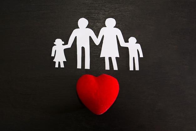 Em uma silhueta de fundo preto de uma família e um coração vermelho. dia mundial da família.