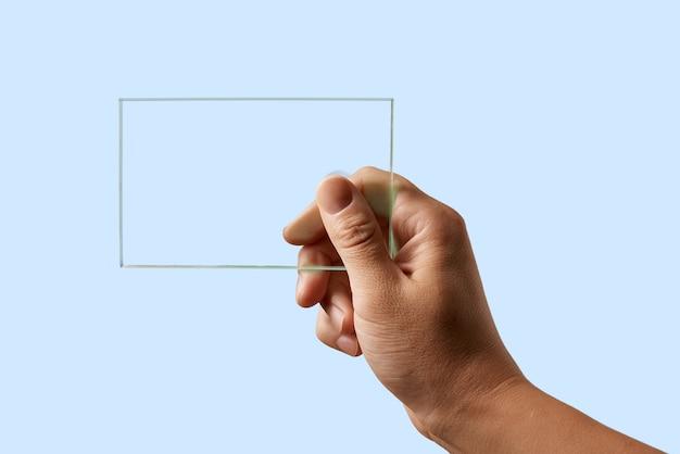 Em uma superfície azul a mão de um homem segura um vidro transparente v