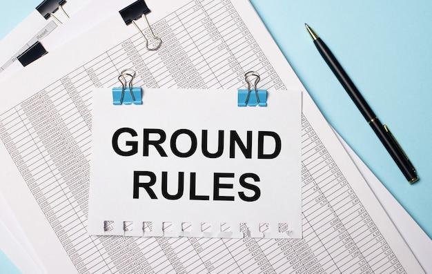 Em uma superfície azul clara, documentos, uma caneta e uma folha de papel em clipes de papel azuis com o texto regras principais