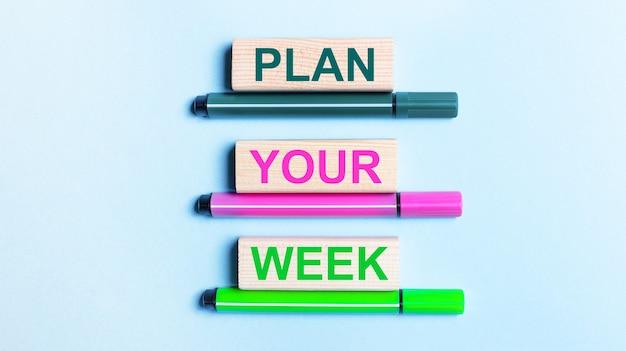 Em uma superfície azul claro, há três canetas hidrográficas multicoloridas e blocos de madeira com o texto planeje sua semana