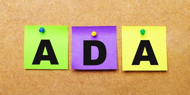 Em uma superfície bege, adesivos multicoloridos para anotações com a palavra ada americans with disabilities act