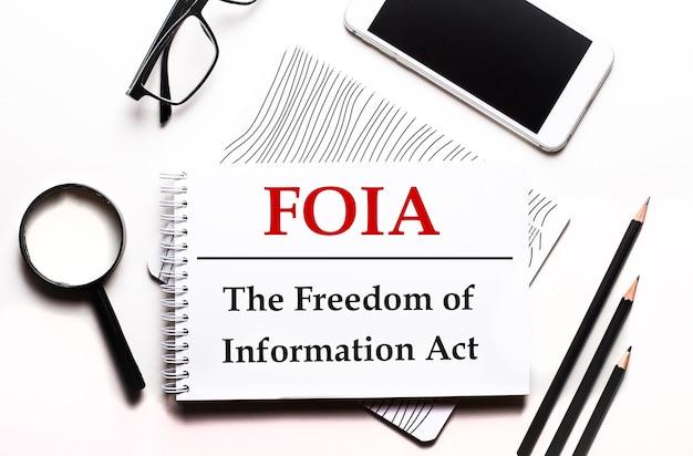 Em uma superfície branca óculos, uma lupa, lápis, um smartphone e um caderno com o texto foia a lei de liberdade de informação.