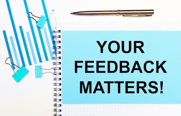 Em uma superfície clara - diagramas em azul claro, clipes de papel e uma folha de papel com o texto seus feedback é importante