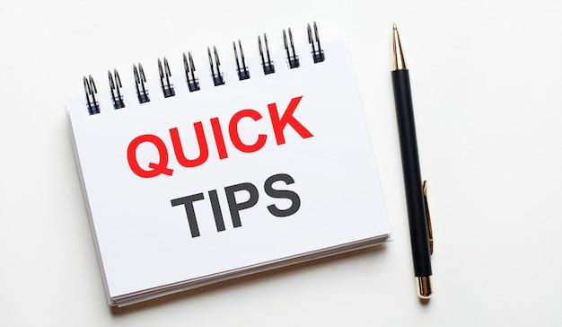 Em uma superfície clara, um caderno branco com palavras quick tips e uma caneta