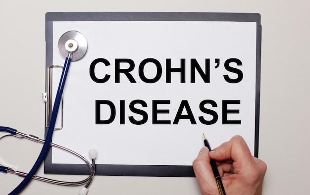 Em uma superfície clara, um estetoscópio e uma folha de papel, na qual um homem escreve crohn é doença