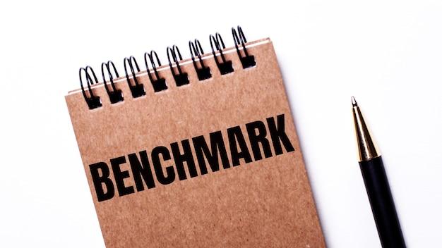 Em uma superfície clara, uma caneta preta e um caderno marrom sobre molas pretas com a inscrição benchmark