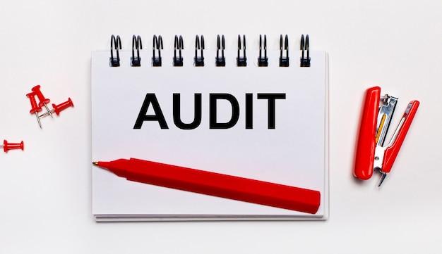 Em uma superfície clara, uma caneta vermelha, um grampeador vermelho, clipes de papel vermelhos e um caderno com a inscrição auditoria