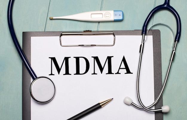 Em uma superfície de madeira azul clara, há um papel rotulado mdma, um estetoscópio, um termômetro eletrônico e uma caneta. conceito médico