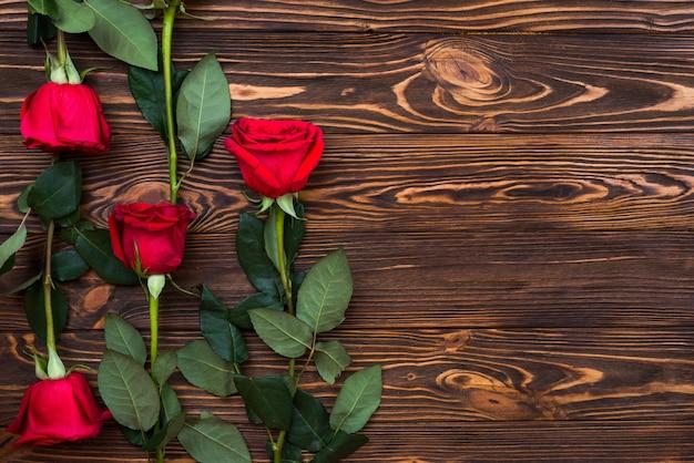 Em uma superfície de madeira são rosas vermelhas