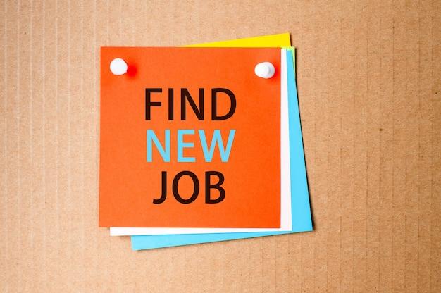 Em uma superfície de papel artesanal - um adesivo quadrado vermelho claro com o texto encontre novo emprego