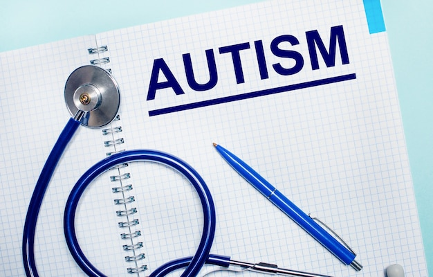 Em uma superfície escura, comprimidos multicoloridos e a palavra autismo em um bloco de madeira. conceito médico