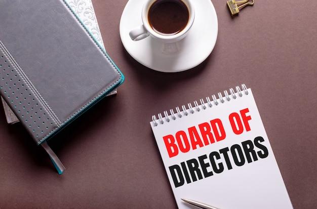 Em uma superfície marrom, diários, uma xícara de café branca e um caderno com conselho de administração