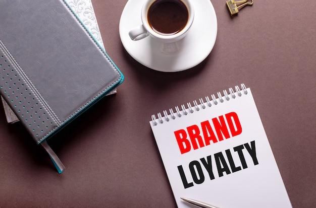 Em uma superfície marrom, diários, uma xícara de café branca e um caderno com o texto lealdade da marca